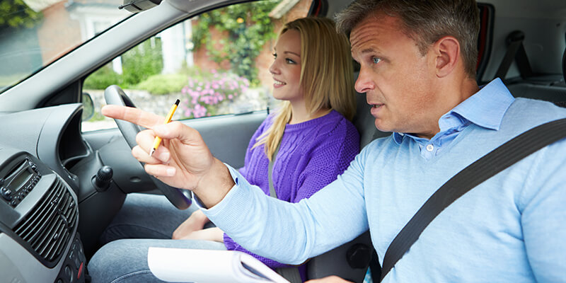 driving instructor with young woman