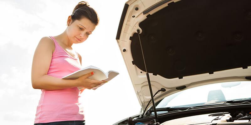 woman looking at vehicle handbook
